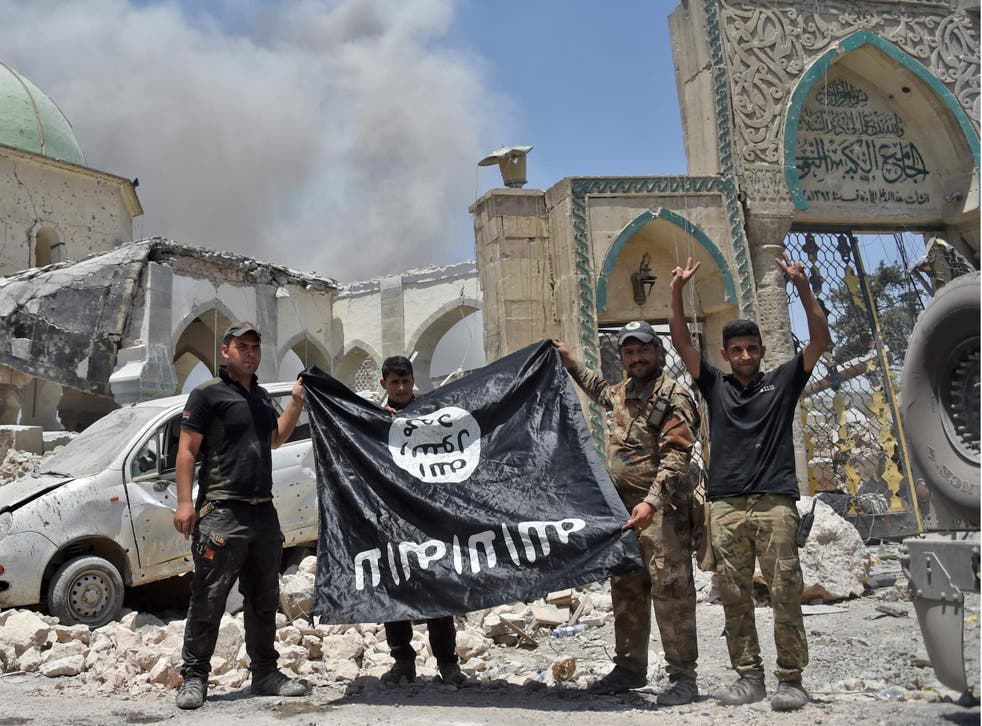 A member of the Iraqi Special Forces raises the victory gesture as others hold upside-down Isis flag outside the destroyed Al-Nuri Mosque in the Old City of Mosul, after the area was retaken