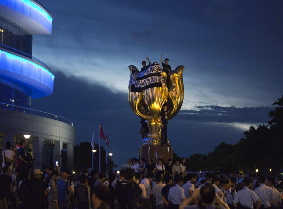 Pro-democracy activists invade the Golden Bauhinia statue in Hong Kong