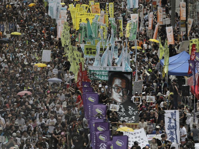 Protesters carry a large image of jailed Chinese Nobel Peace laureate Liu Xiaobo as they march during the annual pro-democracy protest in Hong Kong, Saturday, July 1, 2017