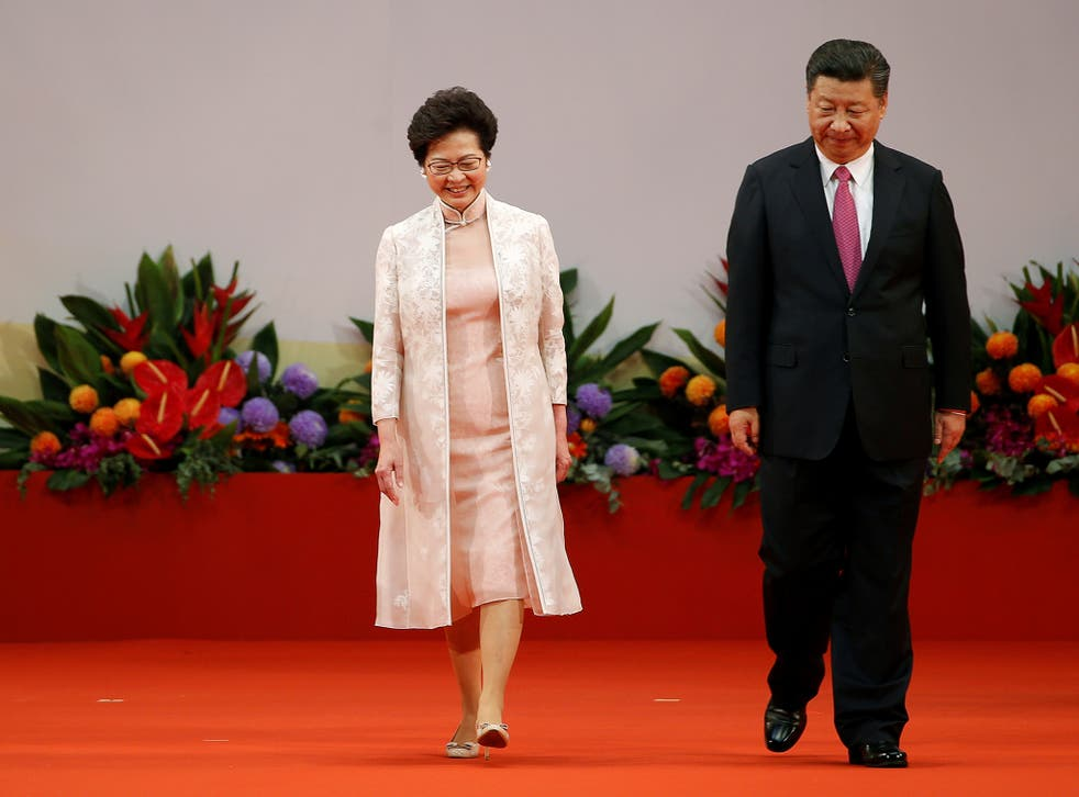 Hong Kong Chief Executive Carrie Lam (L) and Chinese President Xi Jinping walk on the podium during the 20th anniversary of Hong Kong's handover from British to Chinese rule