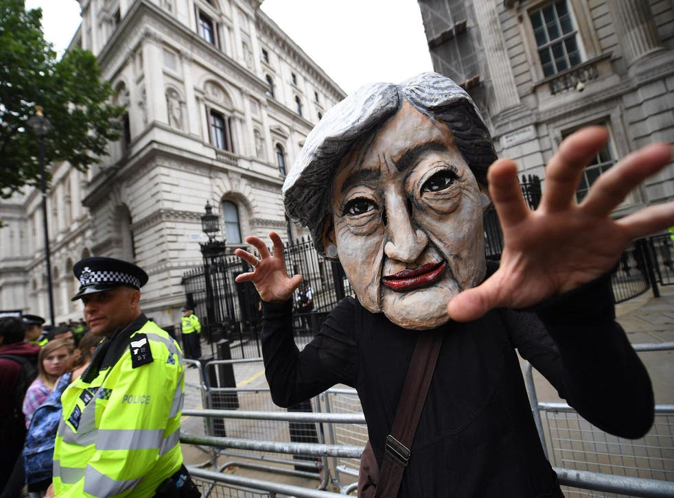A protester wears a Theresa May mask during the 'Not One Day More' march outside of Downing Street on July 1, 2017 in London, England