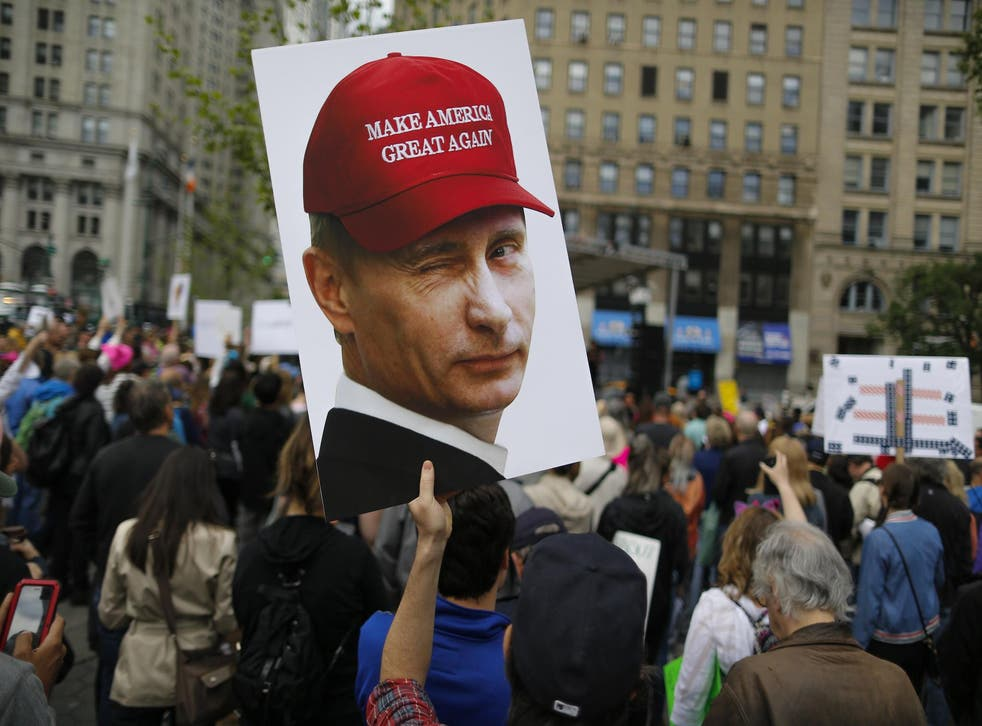 A demonstrator holds up a sign of Vladimir Putin during an anti-Trump 'March for Truth' rally on June 3, 2017 in New York City