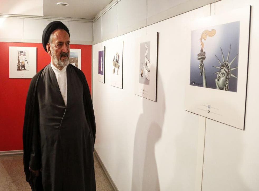Iranian reformist cleric Mahmoud Doaei looks at cartoons of US President Donald J. Trump at an exhibition of the Islamic Republic's 2017 International Trumpism cartoon and caricature contest, in the capital Tehran on July 3, 2017.