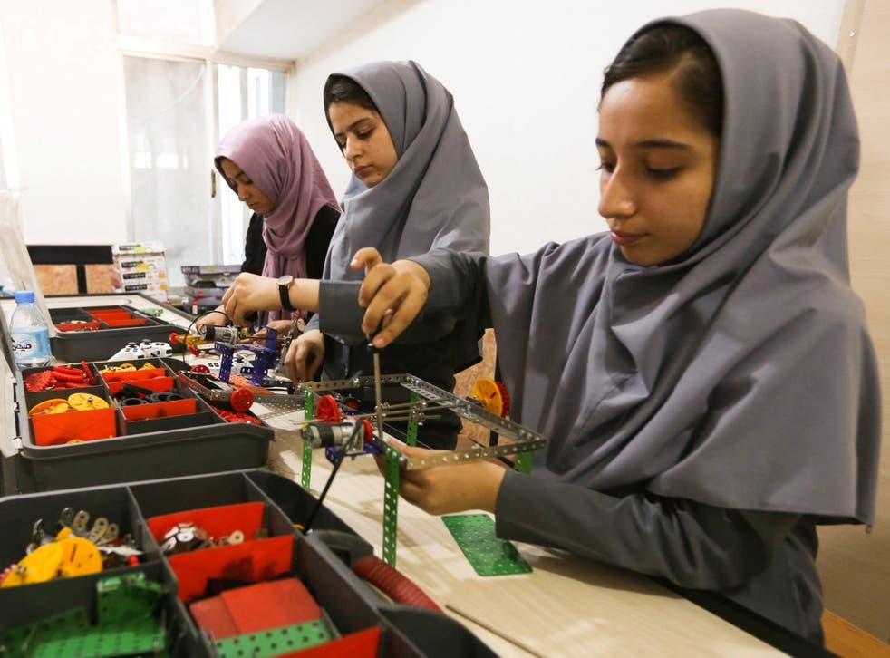 Members of Afghanistan's girls' robotics team work on their machines in Herat, Afghanistan