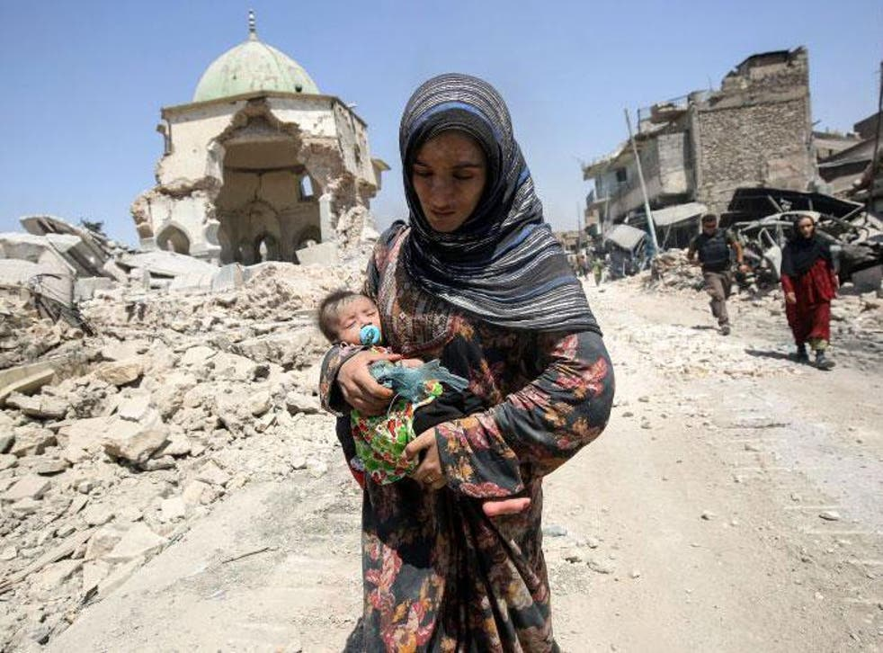 A woman, carrying her baby, flees the Old City of Mosul as Iraqi government forces close in