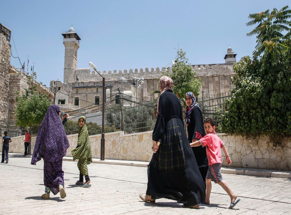 Families walk past the Cave of the Patriarchs, also known as the Ibrahimi Mosque, which is a holy shrine for Jews and Muslims, in the divided city of Hebron in the West Bank