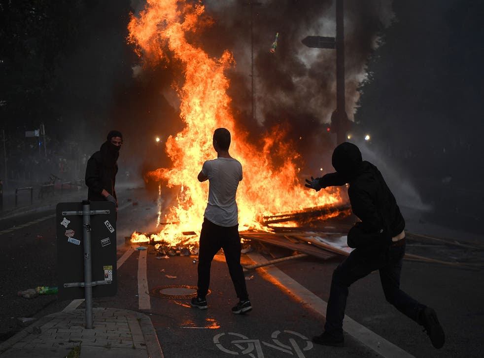 People gather near a fire burning in the middle of town during an anti-G20 protest in Hamburg.