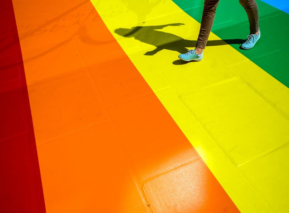 A woman walks past a shop front decorated with the Pride flag colours