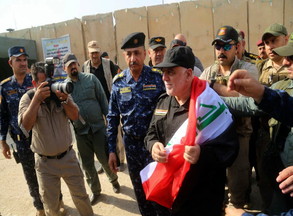 Prime Minister Haider al-Abadi, holding the Iraqi national flag, arrives in Mosul on Sunday
