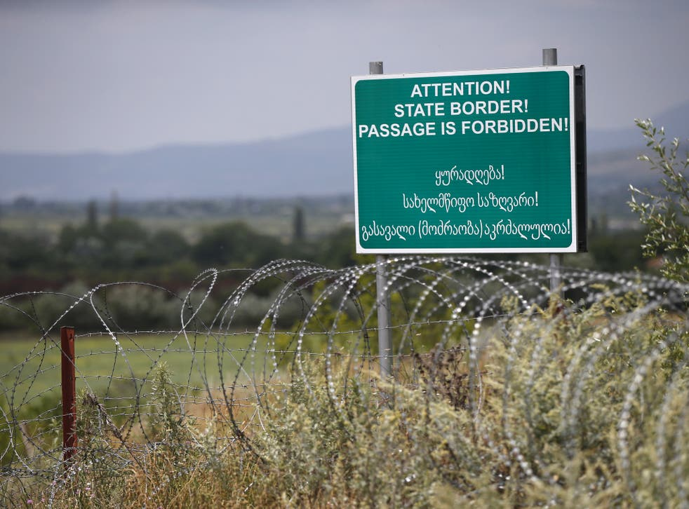 A warning sign is pictured behind a wire barricade erected by Russian and Ossetian troops along Georgia's de-facto border with its breakaway region of South Ossetia in 2015