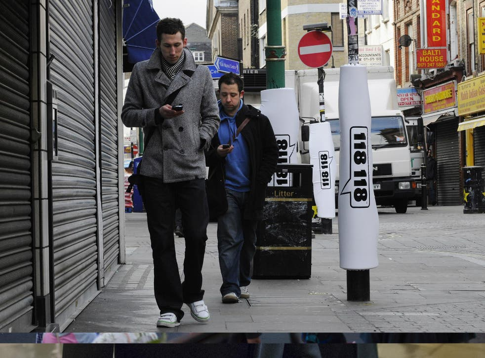 In this photo illustration, two pedestrians walks past padded lamp posts whilst texting in Brick Lane's 'Safe Text' street with padded lamposts.