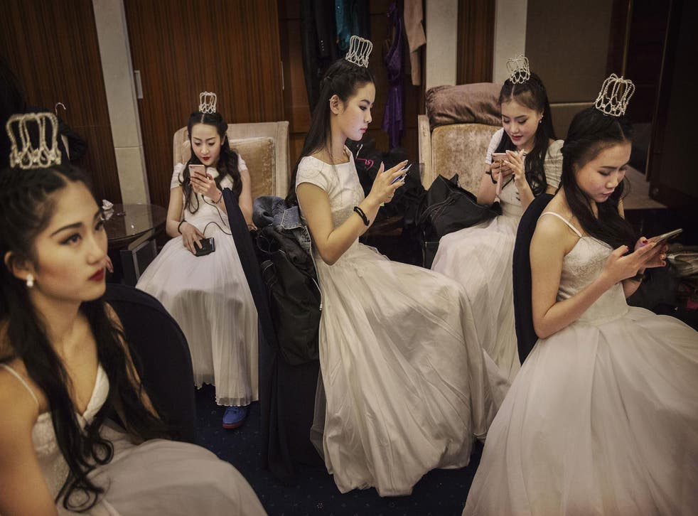 Debutantes from a local academy look at their mobile phones before taking part in the Vienna Ball at the Kempinski Hotel on March 19, 2016 in Beijing, China