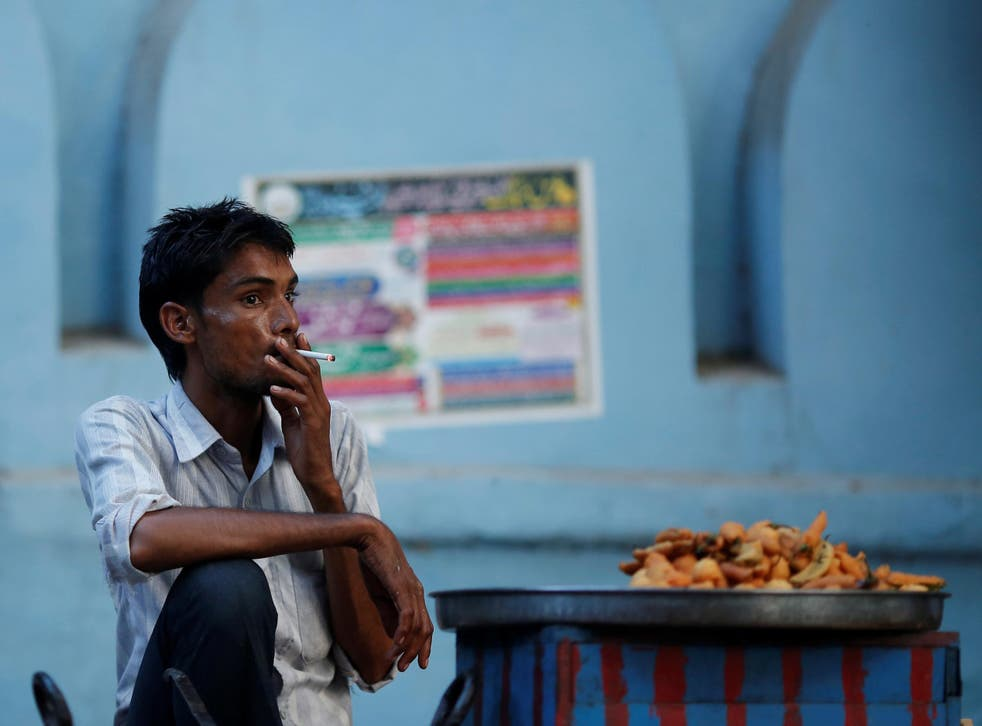 A snack vendor smokes a cigarette as he waits for customers on a street in New Delhi
