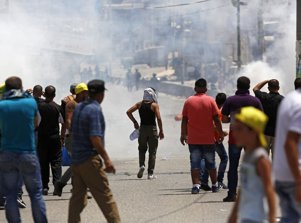 Israeli soldiers fire tear gas at Palestinian protesters during clashes after a protest at Qalandiya checkpoint near the West Bank city of Ramallah on 21 July