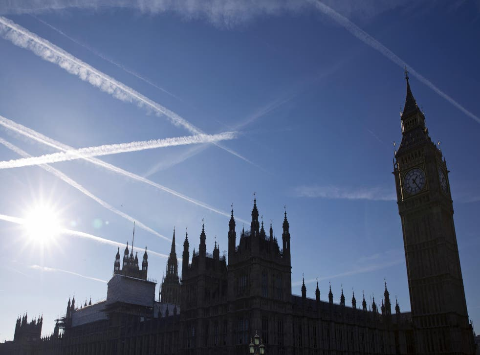 Contrails or vapour trails made by passing aircraft in the sky above the Houses of Parliament