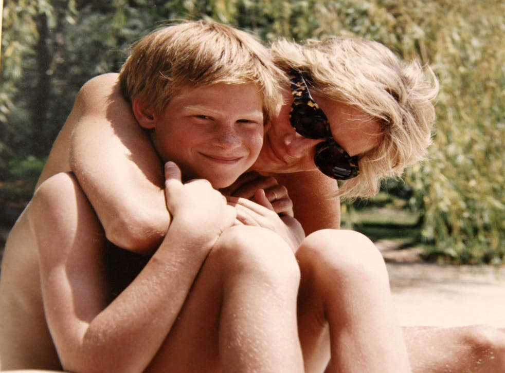 An undated handout picture released by Kensington Palace from the personal photo album of the late Diana, Princess of Wales shows her embracing Prince Harry while on holiday at an undisclosed location
