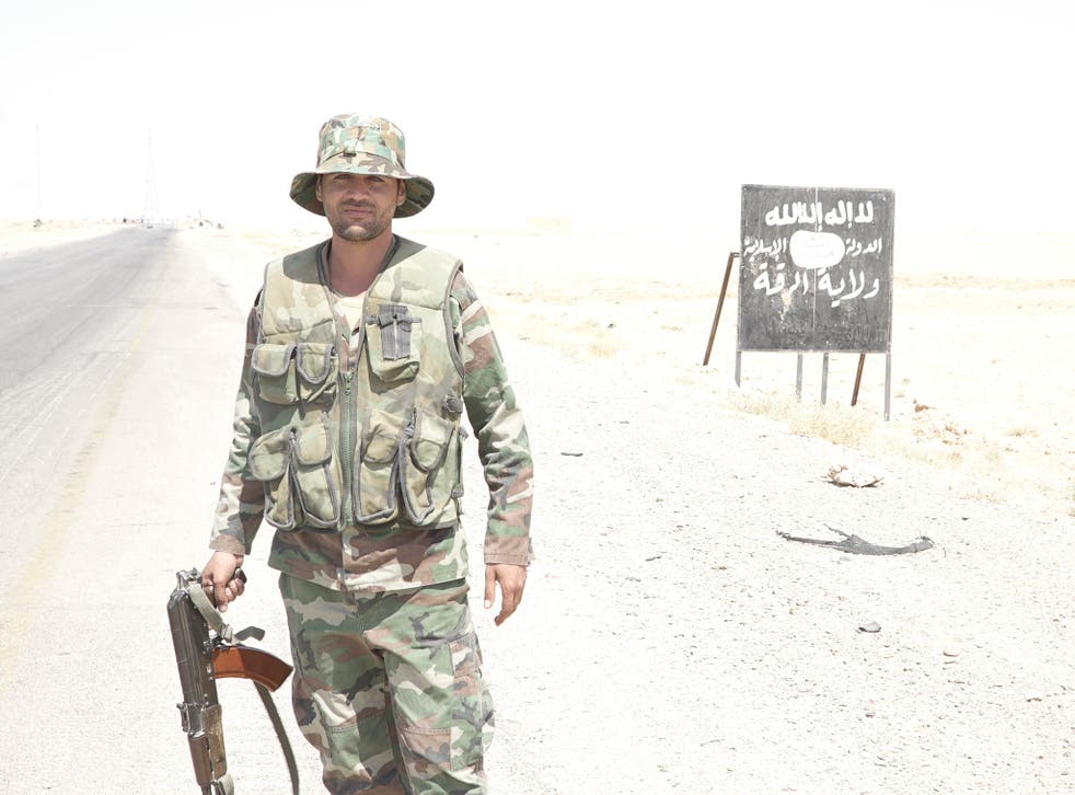 A Syrian soldier in front of a sign on the main road from Homs, 'welcoming' visitors to the Isis 'Caliphate-Province of Raqqa'