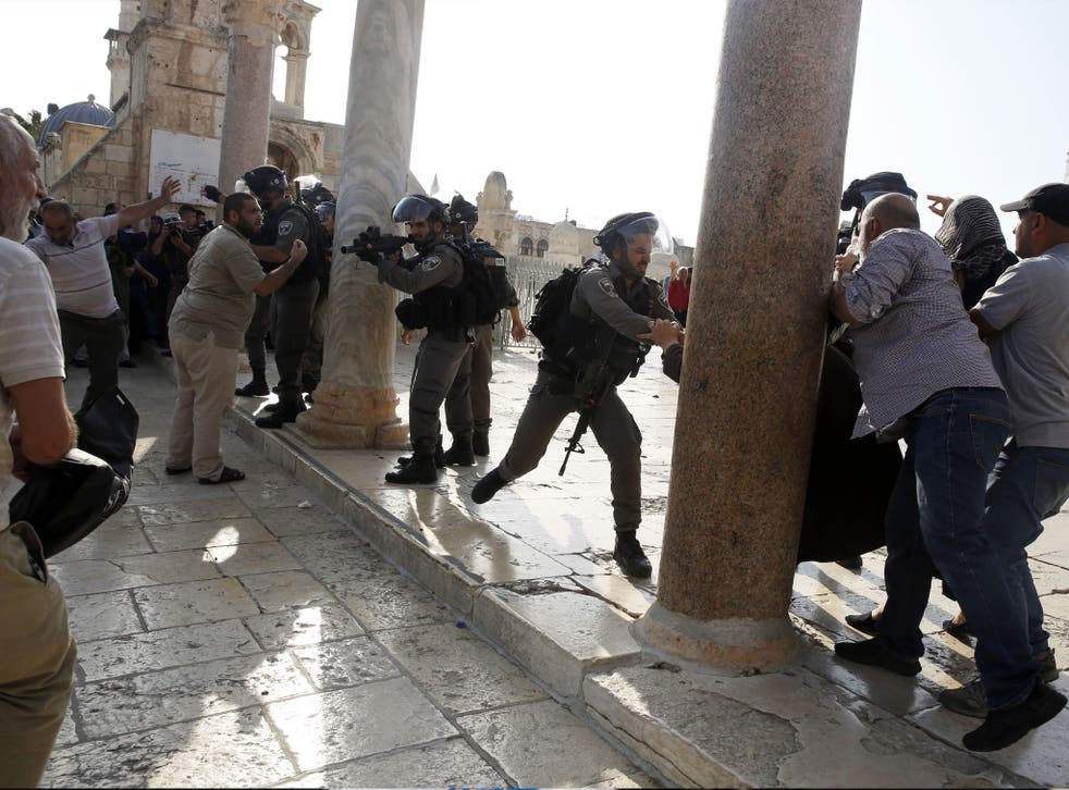 An Israeli police officer aims his weapon at Palestinians during clashes at the Al Aqsa Mosque
