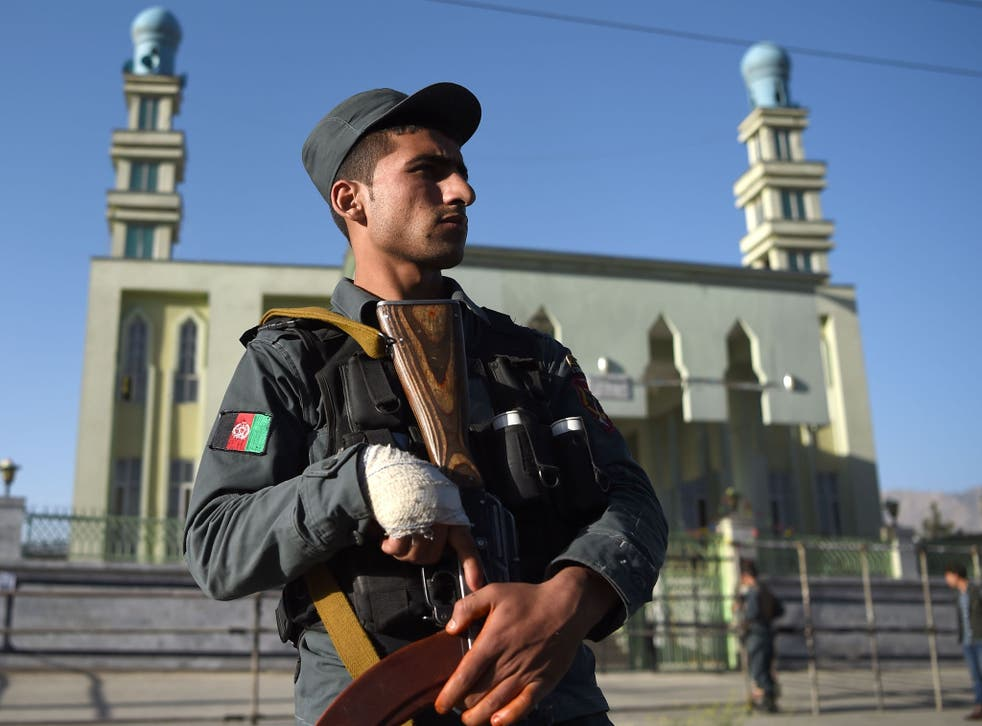 An Afghan policeman outside a Shia mosque in Kabul following a terror attack. The country has been on high alert in the past year as Isis has stepped up sectarian attacks