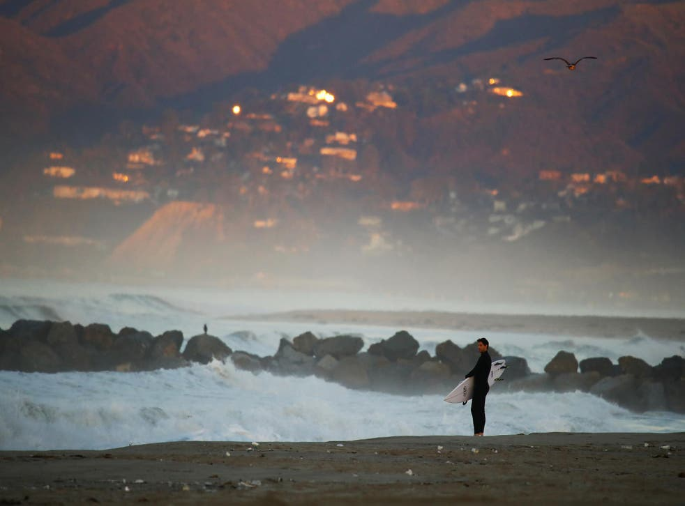 A surfer checks out the waves in Marina del Rey, California