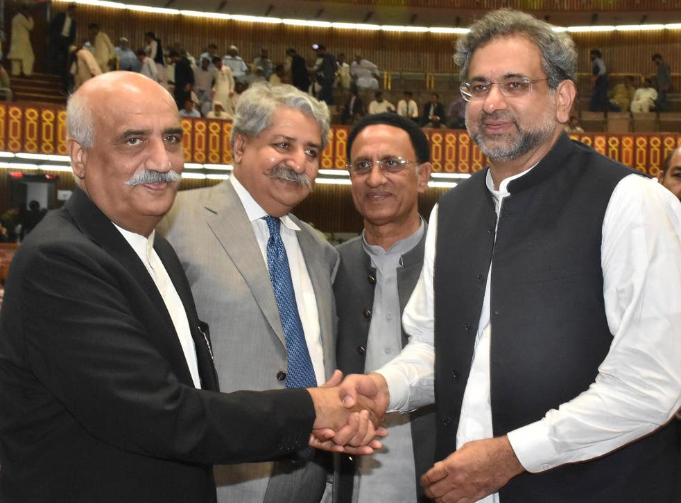 Newly-elected prime minister of Pakistan Shahid Khaqan Abbasi, right, is greeted by the Opposition leader Khursheed Shah, left