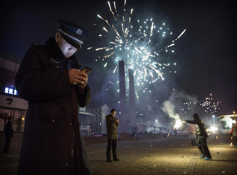 A Chinese security guard checks his smartphone as fireworks explode during celebrations of the Lunar New early on February 19, 2015 in Beijing, China