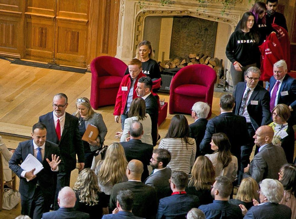 Irish Taoiseach Leo Varadkar (bottom L) walks away from women wearing 'repeal' T-shirts after his speech