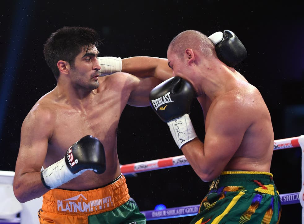 Indian boxer and WBO Asia-Pacific Super Middleweight champion Vijender Singh (L) throws a punch at WBO Oriental Super Middleweight champion of China Zulpikar Maimaitiali during their double title bout at the National Sports Complex of India (NSCI) Dome in Mumbai on August 5, 2017. / AFP PHOTO / PUNIT PARANJPEPUNIT