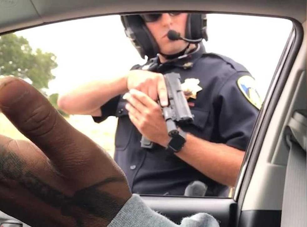 A still from a video apparently recorded by a woman in the car as the male passenger expresses incredulity the officer has drawn his gun