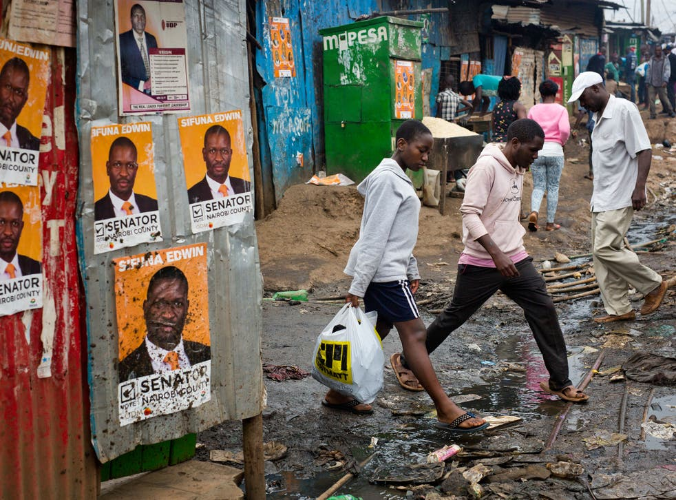 Kenyans walk past election posters in Nairobi's Kibera slum; rising living costs and inadequate healthcare are among the issues facing the country