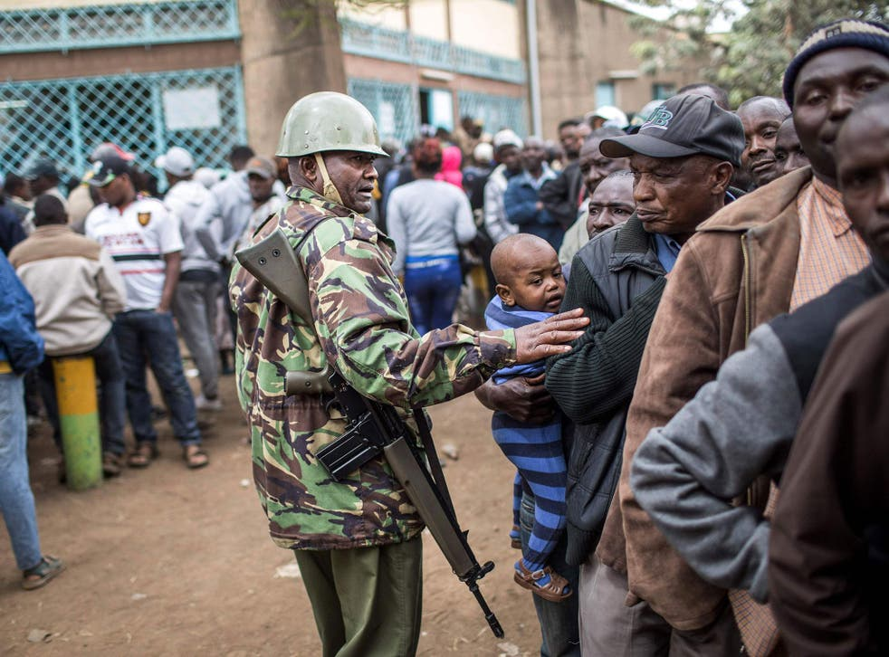 A police officer monitors access to a polling station at Kariokor Community Centre in Nairobi during Kenya's general election
