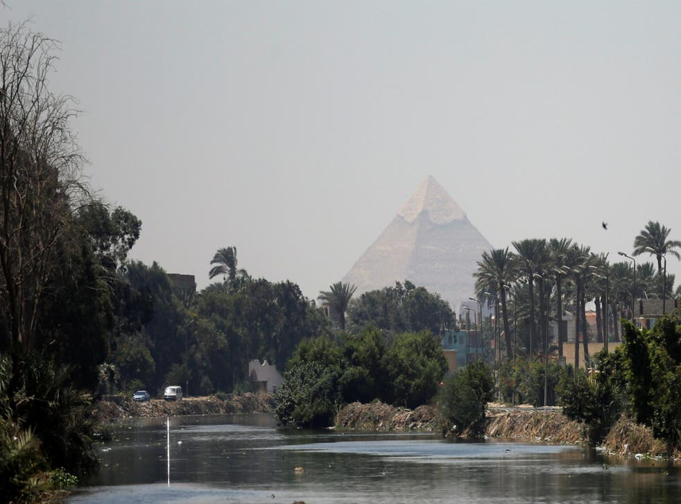 The Pyramid of Khufu, the largest of the Giza pyramids, seen behind a canal which flows into the River Nile on the outskirts of Cairo