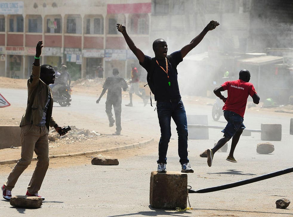 Supporters of Kenya's National Super Alliance shout slogans as they set fire to barricades in Kisumu