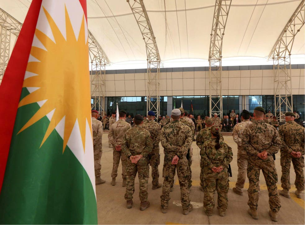 Military advisers from the international coalition forces stand during a transfer of authority ceremony on 15 June 2017 at the Kurdistan Training Coordination Center (KTTC) of Erbil, the capital of the autonomous Kurdish region of northern Iraq.