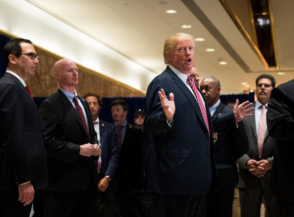 US President Donald Trump speaks to reporters on his way out of the lobby following a meeting on infrastructure at Trump Tower