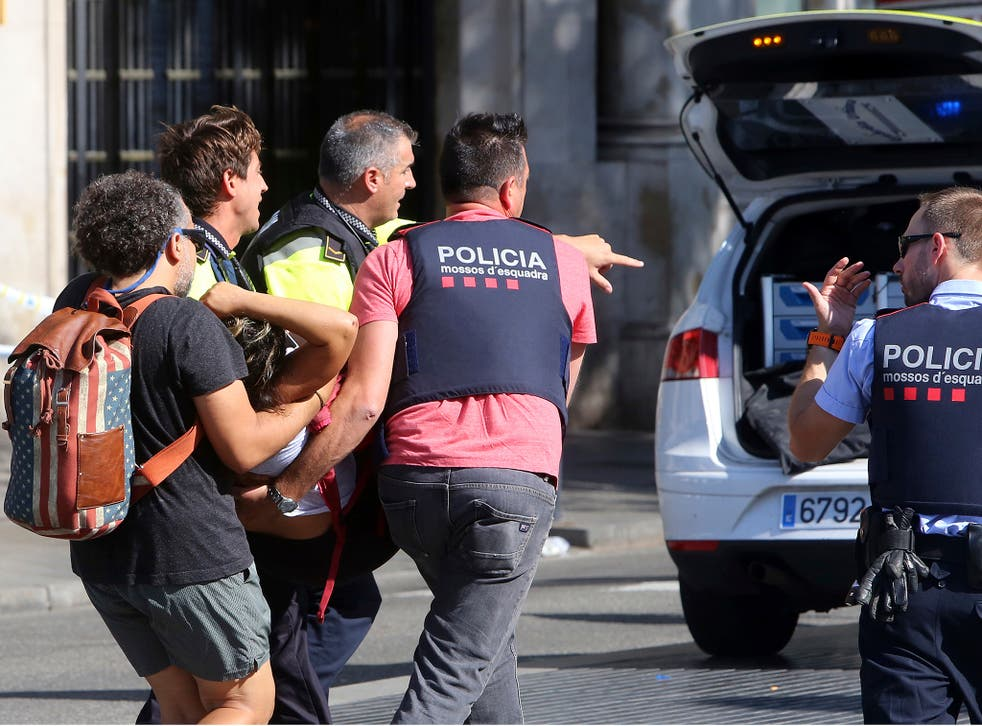 An injured person is carried in Barcelona after a white van jumped the sidewalk in the historic Las Ramblas district