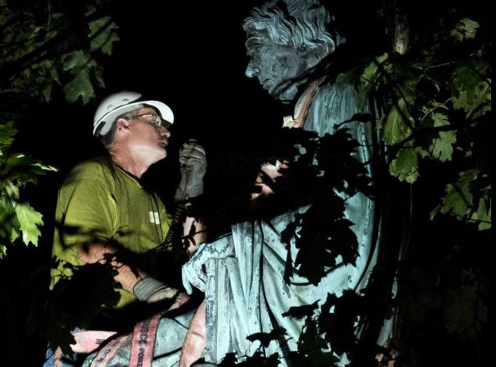 A worker dismantles the statue of Supreme Court Justice Roger B. Taney outside the Maryland State House in Annapolis