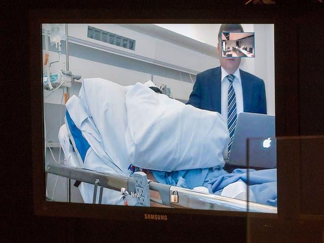 Abderrahman Mechkah covers his face during a court hearing video link