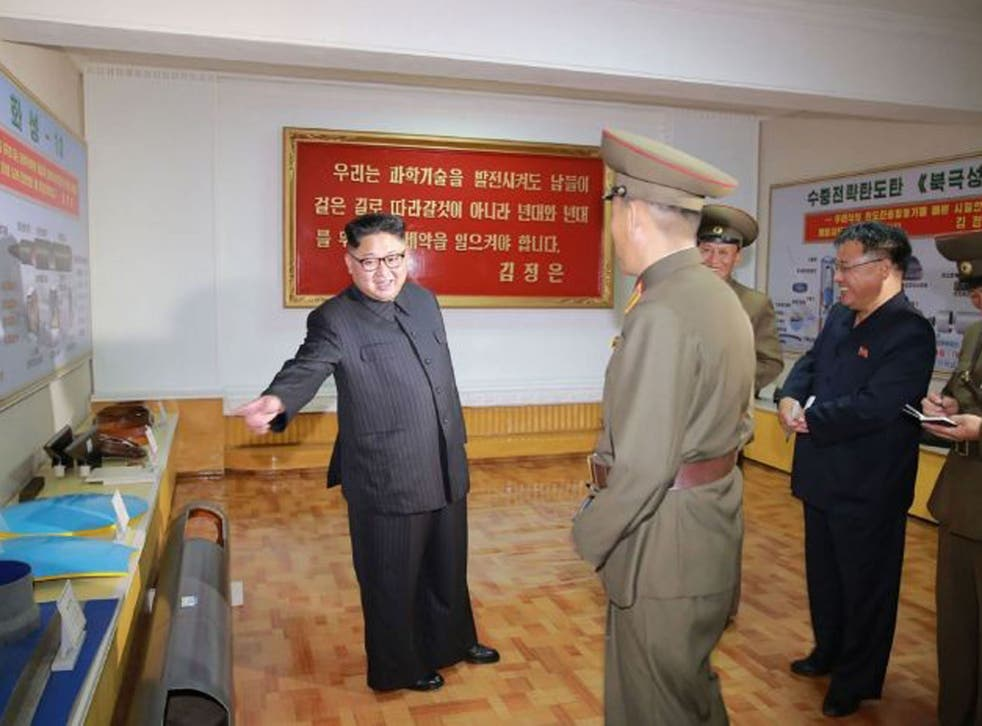 The undated picture shows Kim Jong-un surrounded by plans for new weapons
