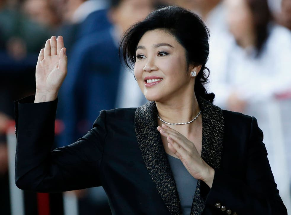 Yingluck Shinawatra waves to supporters as she arrives to deliver closing statements in her trial on 1 August - but has apparently fled before hearing the verdict