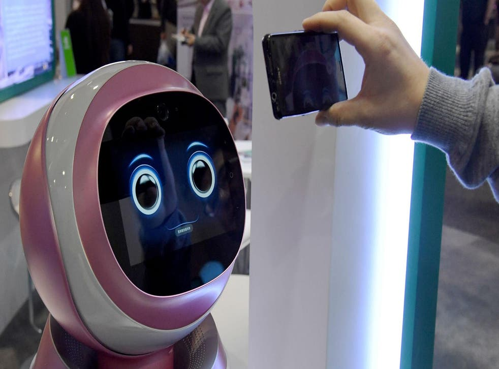 LAS VEGAS, NV - JANUARY 05: An attendee records images of a prototype Kikoo autonomous robot for children made by Hanwuji Intelligence at CES 2017. Picture: