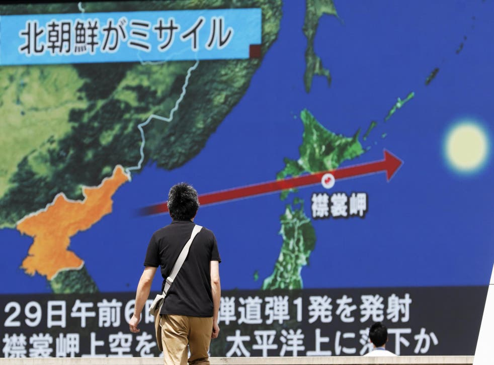 A man looks at a screen in Tokyo displaying a TV news programme reporting North Korea launching a ballistic missile over Japan