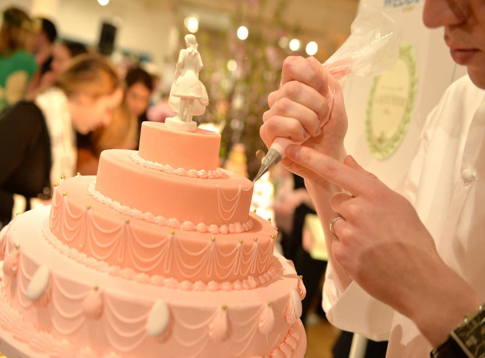 A stock photo of a wedding cake is pictured being worked on