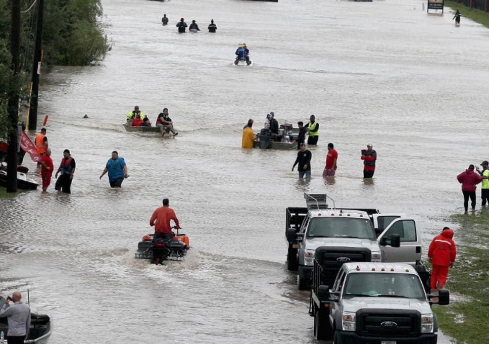 People make their way out of a flooded neighborhood after it was inundated with rain water following Hurricane Harvey