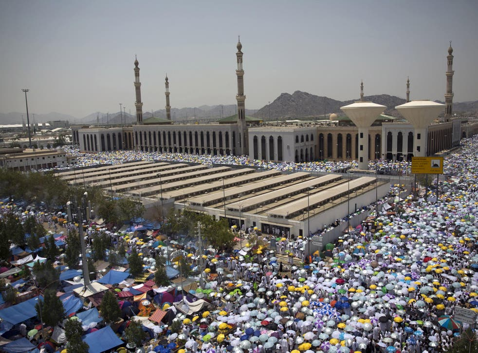 Muslim pilgrims hold umbrellas as they attend noon prayers outside the Namirah mosque on Arafat Mountain during the annual Hajj pilgrimage outside the holy city of Mecca, Saudi Arabia