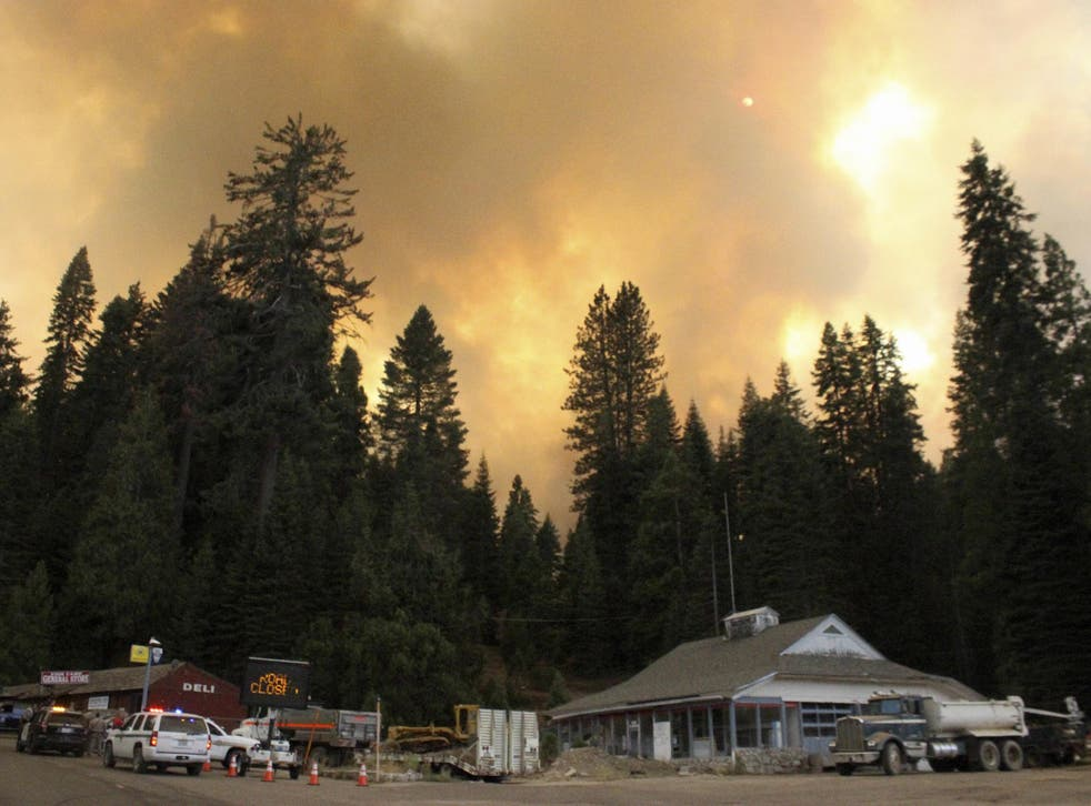 Smoke rises from a wildfire behind the Fish Camp General Store near Yosemite National Park, California