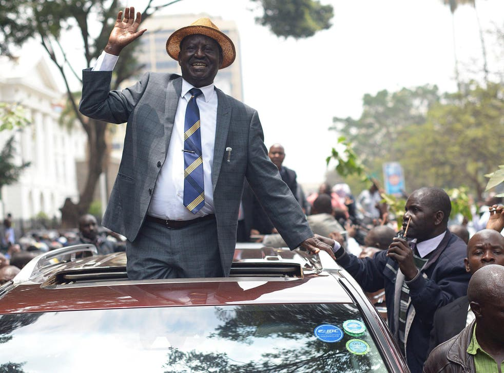 Kenyan opposition leader Raila Odinga waves at supporters as he leaves the Supreme Court
