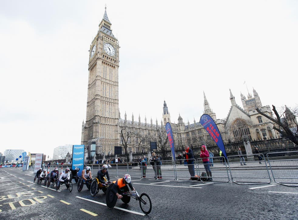 The men's elite wheelchair lead group head past Big Ben during the London Marathon – organisers permit only a dozen ordinary wheelchair racers to take part