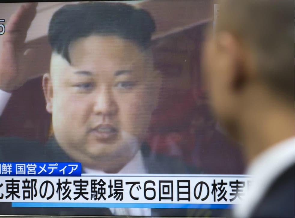 A pedestrian watches a monitor showing an image of North Korean leader Kim Jong-Un in a news program reporting on North Korea's 6th nuclear test on 3 September 2017.