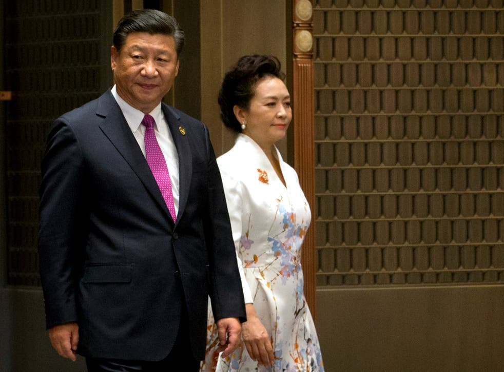 Chinese President Xi Jinping and his wife Peng Liyuan arrive at a summit with Russia, India, Brazil and South Africa in southeast China, with domestic and international issues on his mind Mark Schiefelbein/AP